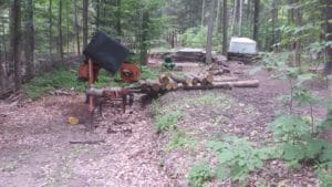 Advance planning will allow arranging logs in a manner to more easily load the sawmill. Creating a cut bank or using a gentle slope makes easy work of loading logs if the sawmill lack hydraulics.