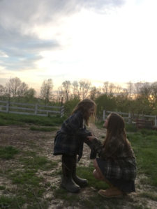 Lianna, age 15, and her little sister Nora, age 8, pose for a picture in their peach orchard at sunset. Taken by Lianna Bonacorsi