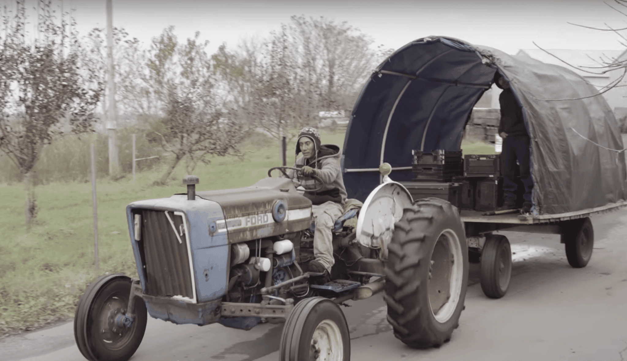 A person driving a tractor hauling a covered bed