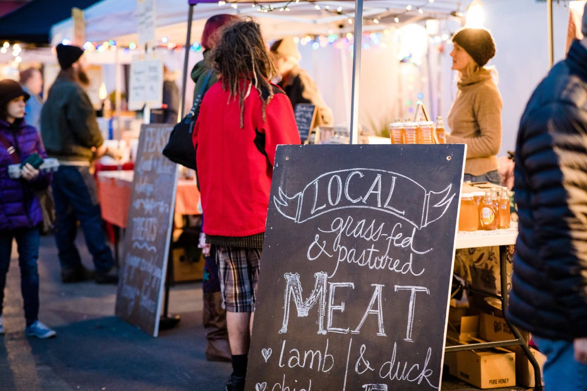 farmers market stand with sign advertising local meat