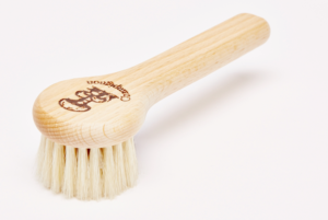 A round wooden brush with course bristles and a handle.