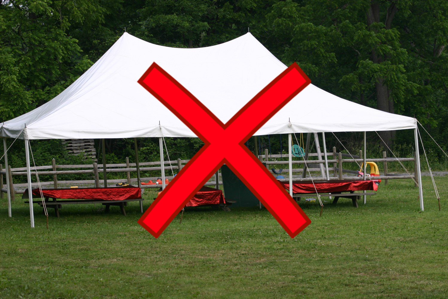 Picnic tables under tent with red x through image