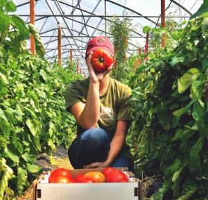 A young woman moved from Missouri to New York and is holding a tomato in front of her face.
