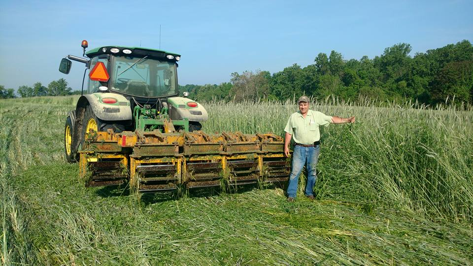 Steve Groff of Cedar Meadow Farm stands next to his tractor, which is pulling a roller-crimper he developed.
