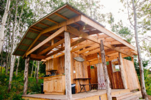 A wooden structure equipped with electricity and light, seasonal plumbing for 2 flush toilets, 2 hot showers, and a simple rustic camp kitchen stocked with dishes, 2-burner propane stove, and basic cooking amenities.