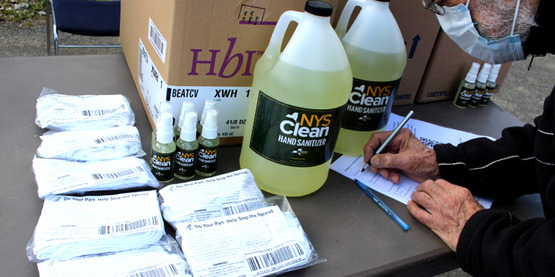 Bottles of hand sanitizer and packages of masks sit on a table, ready to be given to a farmer.