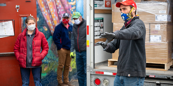 Graham Savio, CCE Tompkins Ag Team Leader, speaks to volunteers before unloading a truck of hand sanitizer and masks destined for Tompkins County farms.