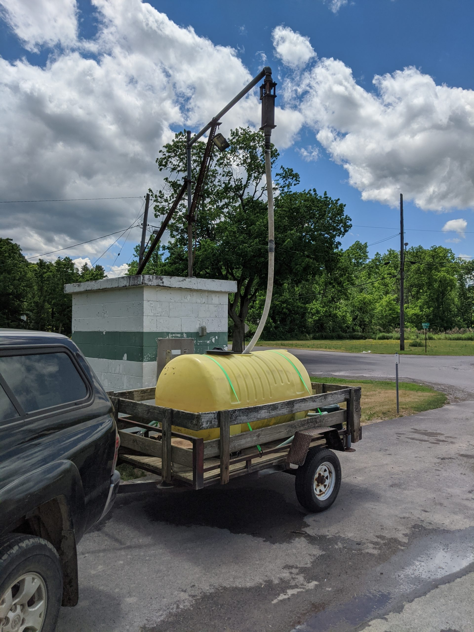 A cylindrical water tank gets filled as it sits in a small wooden trailer.